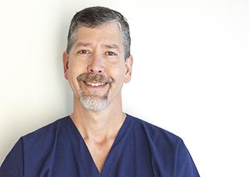 Dr. John smiles against a white background.